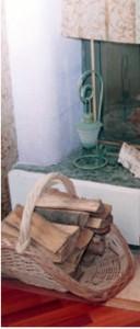 Плетеная дровница с дровами у камина